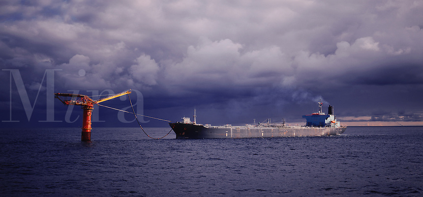 Oil tanker taking on a load of crude from a single point mooring joined by a pipeline to a nearby production platform.  North Sea.