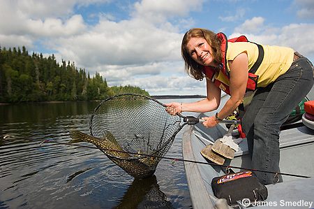 Woman landing a northern pike with a net