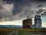 Idaho, Eastern, Tetonia. Grain elevators under stormy skies.