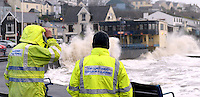 WEATHER PICTRURE WALES<br /> Pictured: Coastguard officers watch on as waves are crashing against the marina wall in Saundersfoot, Pembrokeshire, west Wales. Wednesday 05 February 2014<br /> Re: Severe weather experienced in parts of the UK due to strong winds and high tides. Severe flood warning have been issued by the Environment Agency.