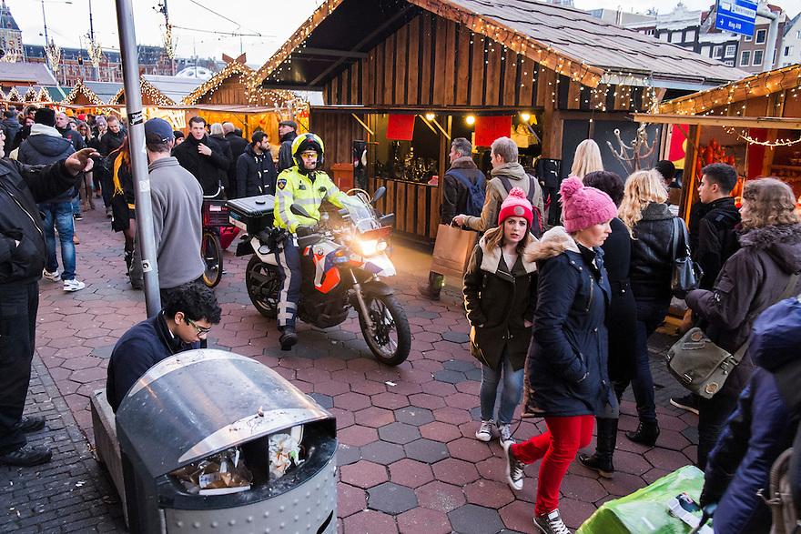 Nederland, Amsterdam, 11 jan 2014<br /> Politie op motor tussen veel winkelend publiek op het Damrak op zoek naar een verdachte <br /> Foto: Michiel Wijnbergh