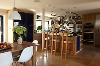 The kitchen is spacious and uncluttered with pans stored on a rack above the kitchen island