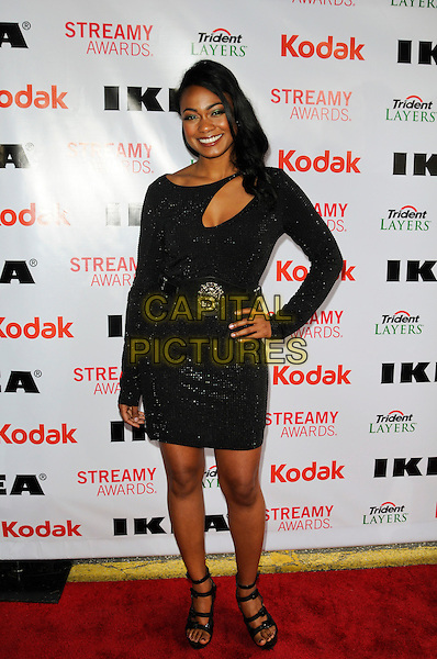 TATYANA ALI.The International Academy of Web Television's 2nd Annual Streamy Awards at the Orpheum Theatre in Los Angeles, California, USA..April 11th, 2010.full length dress waist belt long sleeved sleeves hand on hip strappy shoes sandals platform open toe smiling black cut out cleavage sparkly .CAP/ROT.©Lee Roth/Capital Pictures