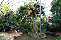 General view of trees and pond inside la grande voliere (the large aviary), a steel latticework domed structure, built in 1888 for the Exposition Universelle (Universal Exposition) of 1889, in the Menagerie of the Jardin des Plantes, Museum National d'Histoire Naturelle, Paris, 5th arrondissement, France. Founded in 1794 by Jacques Henri Bernardin de Saint-Pierre, the Menagerie of Jardin des Plantes became the largest exotic animal collection in Europe in the 19th century and is the second oldest public zoo in the world. Picture by Manuel Cohen