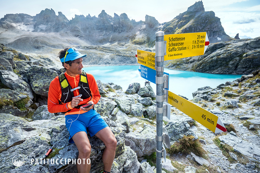 A man sits next to a Swiss trail sign using his phone and map to figure out which way to go, Pizol, Switzerland