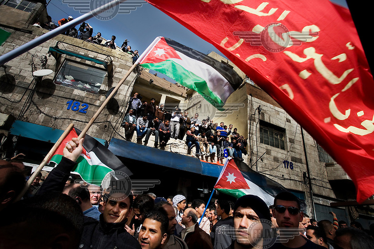 People hold up flags at a demonstration in the centre of Amman against the rule of King Abdullah II.