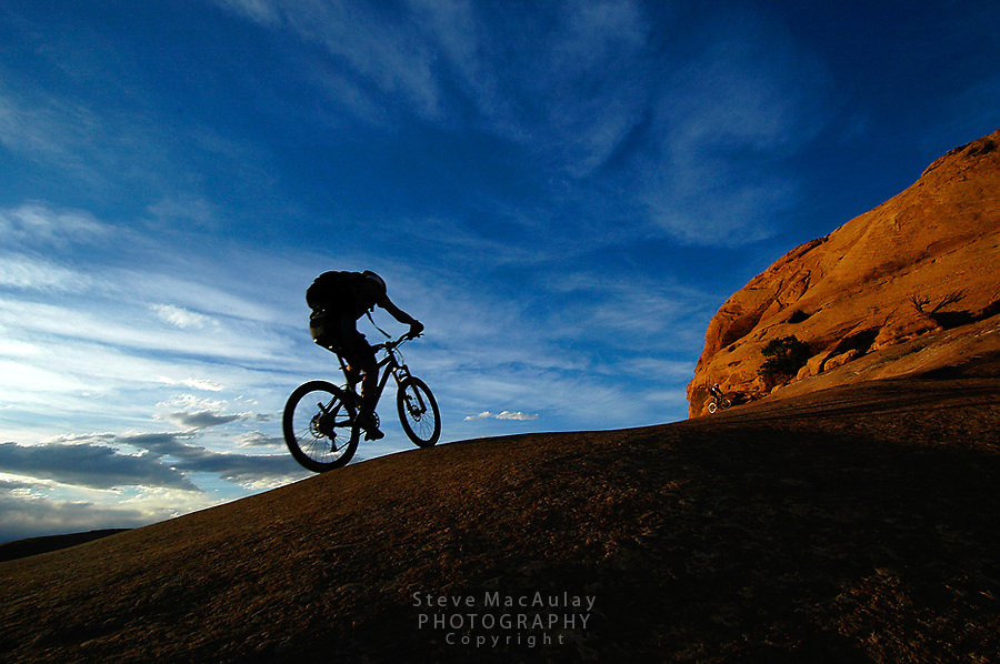 Mountain biker in silhouette climbing slickrock slope as the sun sets, Slick Rock Trail, Moab, Utah