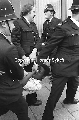 Police arrest youth at the so called Battle of Lewisham, London 13 August1977. 500 members of the National Front marched from New Cross to Lewisham, various counter-demonstrations by approximately 4,000 people led to violent clashes between the two groups and between the anti-NF demonstrators and police. 5,000 police officers were present and 56 officers were injured in the riots, 11 of whom were hospitalised. 214 people were arrested for obstructing the police, threatening behaviour, assault, possession of an offensive weapon and throwing missiles. Later disturbances in Lewisham town centre saw the first use of police riot shields on the UK mainland.