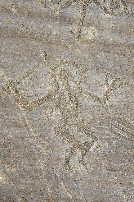 Petroglyph, rock carving, of a warrior dancing carrying with a sword and a round shield and wearing a halo helmet. Carved by the ancient Camuni people in the iron age between 1000-1600 BC. Rock no 24,  Foppi di Nadro, Riserva Naturale Incisioni Rupestri di Ceto, Cimbergo e Paspardo, Capo di Ponti, Valcamonica (Val Camonica), Lombardy plain, Italy