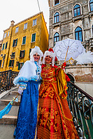 Women in carnival costume on a bridge on  a back canal, Venice Carnival (Carnevale di Venezia), Venice, Italy.