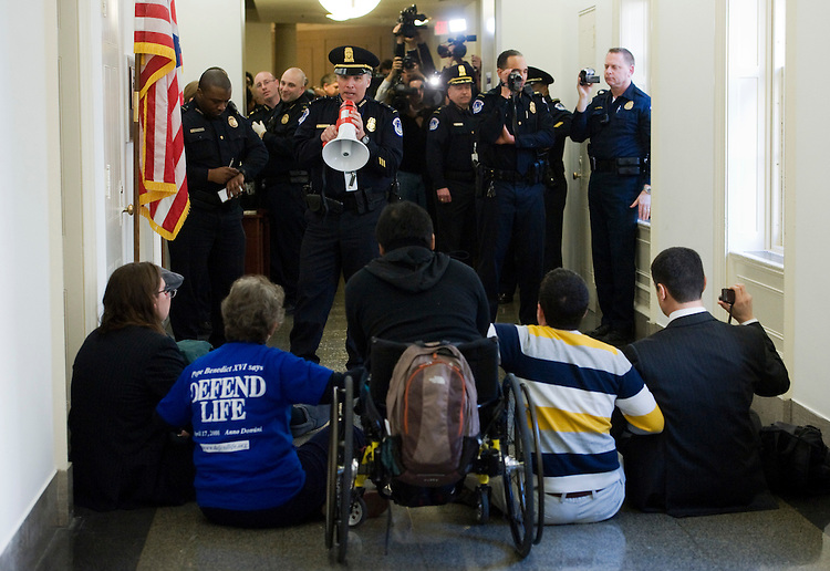 UNITED STATES - FEBRUARY 23:  Capitol Police warn pro-life activists, organized by OverturnRoe, they will be arrested if they continue to stage a sit in outside of the Longworth office of Speaker John Boehner, R-Ohio.  About 6 people were arrested for sitting in the hallway while calling on the defunding of Planned Parenthood.  (Photo By Tom Williams/Roll Call)