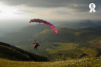 Young man paragliding off hill, rear view (Licence this image exclusively with Getty: http://www.gettyimages.com/detail/200482372-001 )