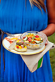 USA, Tennessee, Nashville, Iroquois Steeplechase, woman holding a plate with a bowl of Tomato-Roasted Corn-Avocado Salad