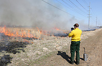 NWA Democrat-Gazette/DAVID GOTTSCHALK  Seth Pickens, Vice President of ECO, Inc., environmental consultant for the city of Fayetteville, photographs an area of burn after using a drip torch Monday, March 18, 2019, during a prescribed burn at the Woolsey Wet Prairie Sanctuary in Fayetteville. The prescribed burn serves as a vegetation management effort to maintain the plant community. Baseline monitoring identified 47 plant species at the site in 2005. At the end of the 2018 growing season, 482 plant species have been observed, 11 of which are species of special concern that are tracked by the Arkansas Natural Heritage Commission.