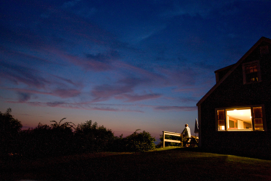 A resident watches the sunset in the fishing port of Menemsha in Chilmark, on the Massachusetts islands of Martha's Vineyard.........................