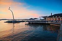 Brygga i skymningen vid Nacka Strand med restaurant och pir med Milles skulptur