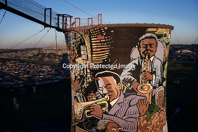 SOWETO, SOUTH AFRICA JANUARY 4: A view of the Orlando Power Station on January 4, 2013 in the Orlando section of Soweto. It not operating but has become a popular spot for visitors as they offer Bungee jumping, and have a restaurant and bar. Soweto today is a mix of old housing and newly constructed townhouses. A new hungry black middle-class is growing steadily. Many residents work in Johannesburg but the last years many shopping malls have been built, and people are starting to spend their money in Soweto. (Photo by: Per-Anders Pettersson)