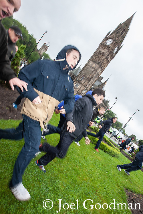 © Joel Goodman - 07973 332324 . 09/06/2012. Rochdale , UK. EDL supporters run across a park opposite Rochdale Town Hall . The English Defence League ( EDL ) hold a march and rally in Rochdale Town Centre . Photo credit : Joel Goodman