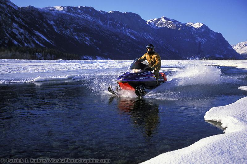 Snow mobile across open water on the nizina river, Wrangell St. Elias National Park, Alaska