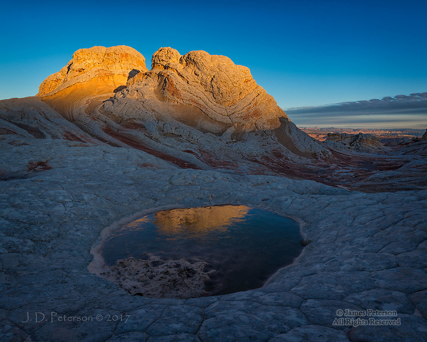 Sunrise at White Pocket, Arizona ©2017 James D Peterson.  In the Vermilion Cliffs National Monument, dawn's light on rugged sandstone peaks is reflected in a frozen pool.