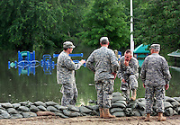 Members of the Iowa National Guard confer atop a levee protecting the Birdland neighborhood from flood water Thursday evening, June 12, 2008 in Des Moines.
