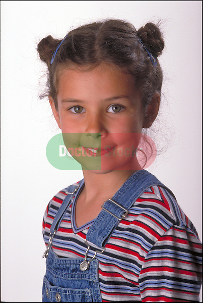 portrait of smiling young girl in overalls