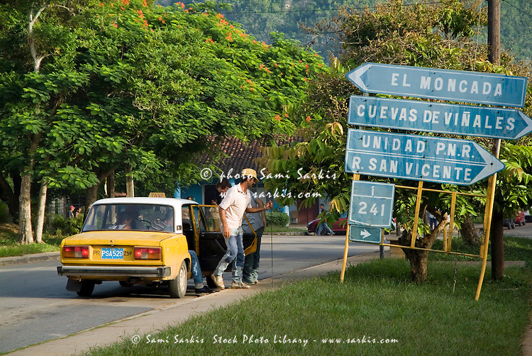 Cuban people getting out of a taxi near road signs in Vinales, Cuba.