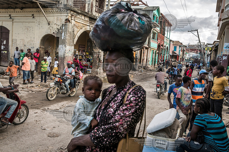 A woman and her child make their way along a crowded street in the town of Jeremie which suffered severe damage after Hurricane Matthew hit the the southwest peninsula. Hurricane Matthew, the first category 5 Atlantic hurricane since 2007, hit the island on 4 October 2016. Winds of up to 230km/h (145mph) tore across the worst affected areas, mainly in the south of the island, killing around over 1,000 people and leaving hundreds of thousands in need of assistance.