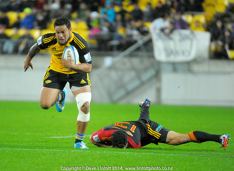 Alapati Leiua slips the tackle of Charlie Ngatai during the Super Rugby match between the Hurricanes and Chiefs at Westpac Stadium, Wellington, New Zealand on Saturday, 24 May 2014. Photo: Dave Lintott / lintottphoto.co.nz