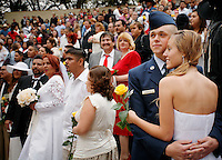 """""""We do!"""" said 400 couples on San Antonio's romantic River Walk during Valentine's Day mass weddings. This annual exchange of love draws couples from across the nation to one of the country's most passionate cities. Here, Ryan and Elsa Foote, right, wed as Ryan prepares for his first assignment for the US Air Force. (Darren Abate/pressphotointl.com)"""