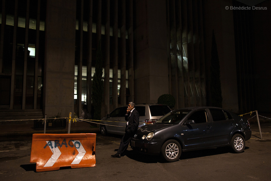 """Donovan leans on the hood of his car and smokes a cigarette behind the Attorney General's Office in Mexico City on May 31, 2015. Donovan Tavera, 43, is the director of """"Limpieza Forense México"""", the country's first and so far the only government-accredited forensic cleaning company. Since 2000, Tavera, a self-taught forensic technician, and his family have offered services to clean up homicides, unattended death, suicides, the homes of compulsive hoarders and houses destroyed by fire or flooding. Despite rising violence that has left 70,000 people dead and 23,000 disappeared since 2006, Mexico has only one certified forensic cleaner. As a consequence, the biological hazards associated with crime scenes are going unchecked all around the country. Photo by Bénédicte Desrus"""