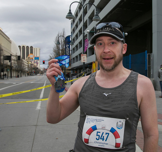 Marathon winner Christopher Robinette shows off his medal during the 6th Annual Reno 5000 Downtown River Run on Saturday, April 6, 2019.