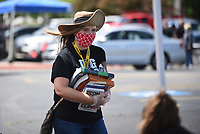 Debbie Alsip, an english teacher at Springdale High School, helps collect text and library books Monday, May 18, 2020, during the Springdale High School Bulldog Bash at the High School. Seniors were given the opportunity to drop off school materials, pick up signs and receive cords and awards. The event kicked off the 12 Days of Graduation event. Check out nwaonline.com/200519Daily/ and nwadg.com/photos for a photo gallery.<br /> (NWA Democrat-Gazette/David Gottschalk)