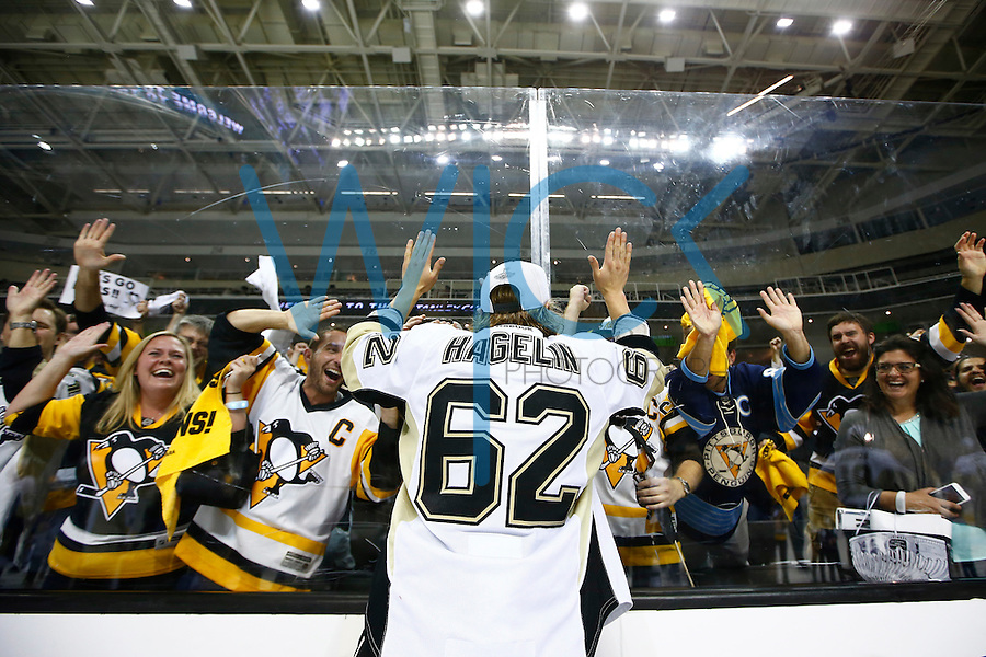 Carl Hagelin #62 of the Pittsburgh Penguins celebrates with the fans along the glass following their 3-1 win against the San Jose Sharks during game six of the Stanley Cup Final at SAP Center in San Jose, California on June 12, 2016. (Photo by Jared Wickerham / DKPS)