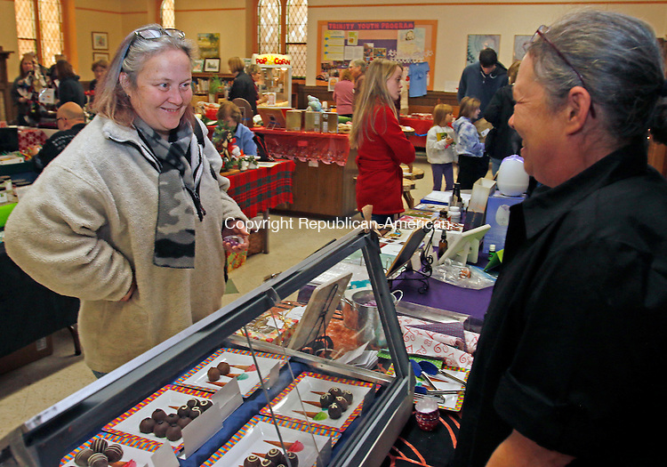 Torrington, CT-11 November 112115MK10 Karla Woodworth (left) talks to Lisa McDonald, from Underground Truffles, about the various treats for sale during the Christmas Fair at Trinity Episcopal Church in Torrington Saturday afternoon.  Naomi Cardello, co-chair of the fundraising committee, said that twenty vendors participated in the yearly tradition to help raise funds for the church's capital campaign. Michael Kabelka / Republican-American