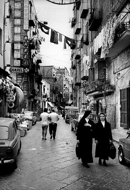 Friends and nuns walk over historic narrow stone streets, with hanging laundry, in the large market area of Naples,Italy.