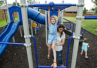 Audrey Killebrew, 7, makes her way across the monkey bars Friday, June 26, 2020, with help from her mom Whitney Killebrew at the park in their Bentonville neighborhood. Go to nwaonline.com/200627Daily/ to see more photos.<br /> (NWA Democrat-Gazette/Ben Goff)