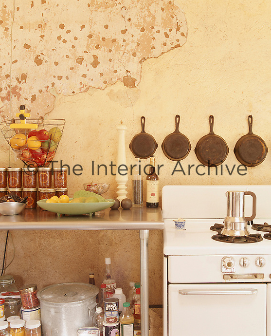 A row of cast iron pans is displayed on the adobe wall behind the antique cooker in the kitchen