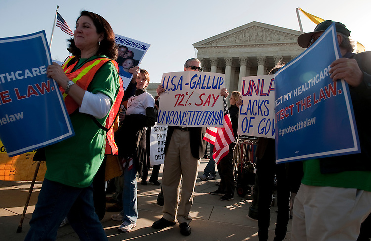 UNITED STATES - MARCH 26:  Pro and anti-health care law demonstrators hold signs outside of the Supreme Court on the first day of opening arguments that will determine the constitutionality of President Barack Obama's health care law.  (Photo By Tom Williams/CQ Roll Call)