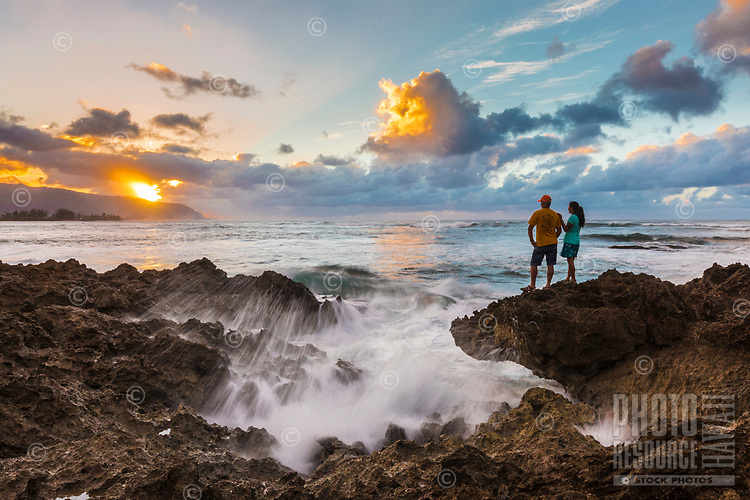 A couple enjoys the sunset on the North Shore of O'ahu.