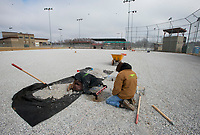 NWA Democrat-Gazette/CHARLIE KAIJO Nick Carter of El Dorado Springs, Mo. (from left) pictured with a man who only wanted to be called Chuck installs the base for a new synthetic turf on Monday, January 8, 2018 at the baseball field in Memorial Park in Bentonville. Mid America Sports Construction has a contract to instal synthetic turf to four of the baseball fields at the park. Carter said the park gets a lot of rain cancellations. The new turf he said will be able to accept more water. They are installing a seven inch gravel base underneath a one-inch synthetic turf. <br /><br />They are scheduled to finish around the second week of February before games and tournaments start up again.