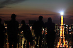 A aerial night view of Eiffel Tower La tour eiffel with people in foreground. City of Paris. Paris. France