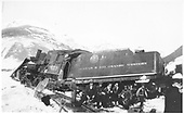 Fireman's-side view of D&amp;RGW #459 derailed in snow south of Silverton.  Nine people, men and boys, sitting by derailed engine.<br /> D&amp;RGW  Silverton (s. of), CO  ca. 1937-1939