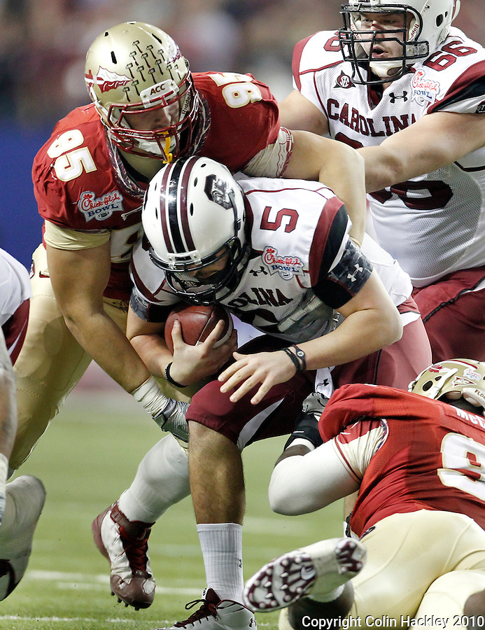 ATLANTA, AG 12/31/10-FSU-SC FB10 CH-Florida State's Bjoern Werner, left, and Anthony McCloud tackle South Carolina's Stephen Garcia during first half action Friday at the Chick-fil-A Bowl in Atlanta..COLIN HACKLEY PHOTO