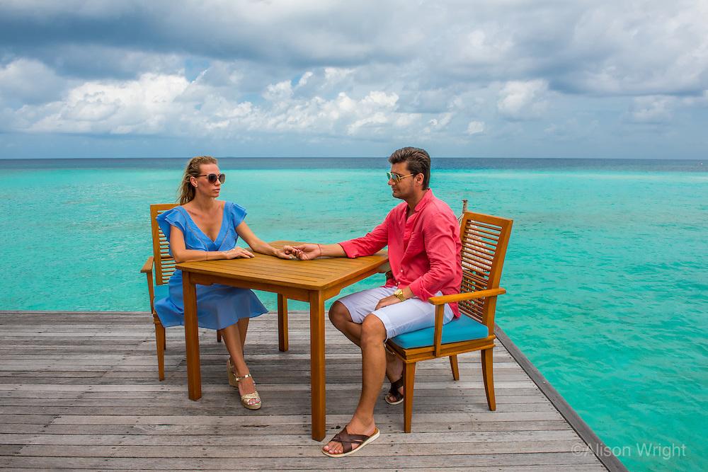 Maldives, Rangali Island. Conrad Hilton Resort. Couple at the Mandhoo organic restaurant over the ocean (MR).