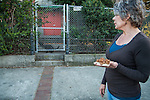 A volunteer for H.A.R.P. (Homeless Animal Response Program), of Antioch, prepares to feed cats  in Antioch, California, on Friday, March 21, 2014.  Photo/Victoria Sheridan