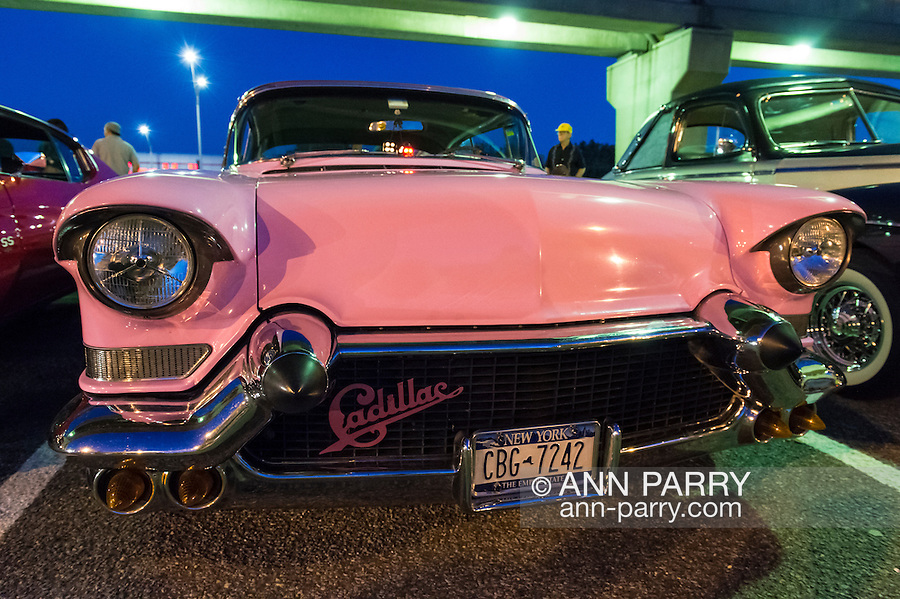 Bellmore, New York, USA. 7th August 2015. A 1957 pink Cadillac, with a front grill Cadillac badge, is on parked near the elevated train tracks at the Friday Night Car Show held at the Bellmore Long Island Railroad Station Parking Lot. Hundreds of classic, antique, and custom cars were on view at the free weekly show, sponsored by the Chamber of Commerce of the Bellmores.