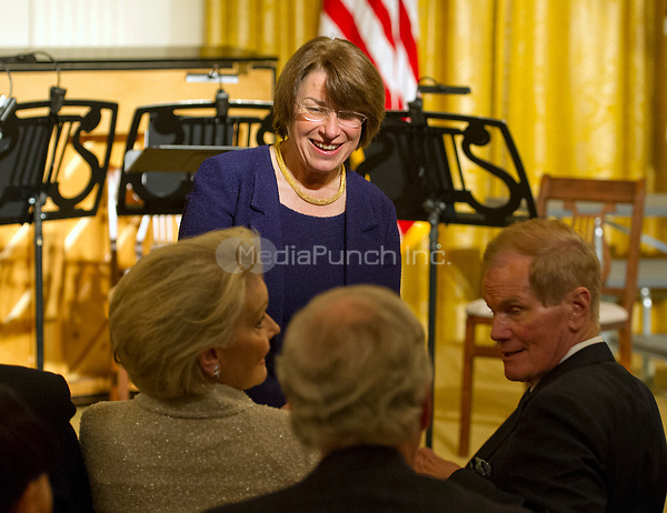 United States Senator Amy Klobuchar (Democrat of Minnesota), top center, and US Senator Bill Nelson (Democrat of Florida), right, in conversation prior to the arrival of US President Donald J. Trump at a reception for US Senators and their spouses in the East Room of the White House in Washington, DC on Tuesday, March 28, 2017.<br /> Credit: Ron Sachs / Pool via CNP /MediaPunch