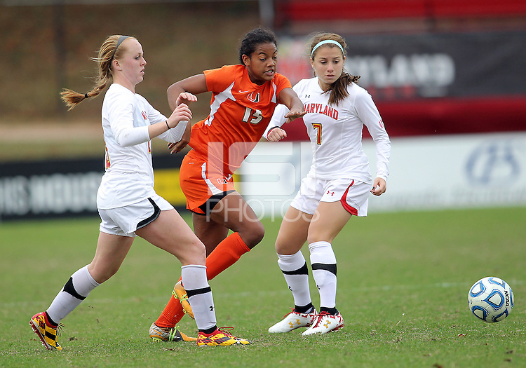 COLLEGE PARK, MD - OCTOBER 28, 2012:  Danielle Hubka (34) and Alex Reed (7) of the University of Maryland try to stop Blake Stockton (29) of Miami during an ACC  women's tournament 1st. round match at Ludwig Field in College Park, MD. on October 28. Maryland won 2-1 on a golden goal in extra time.