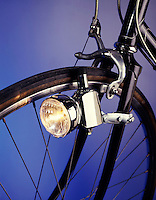 BLOCK GENERATOR POWERS BICYCLE LAMP<br /> Using Friction To Act As A Dynamo<br /> The friction of running against the tire creates mechanical energy which is changed into electrical energy powering the lamp.  Closeup shows sidepull Caliper brakes